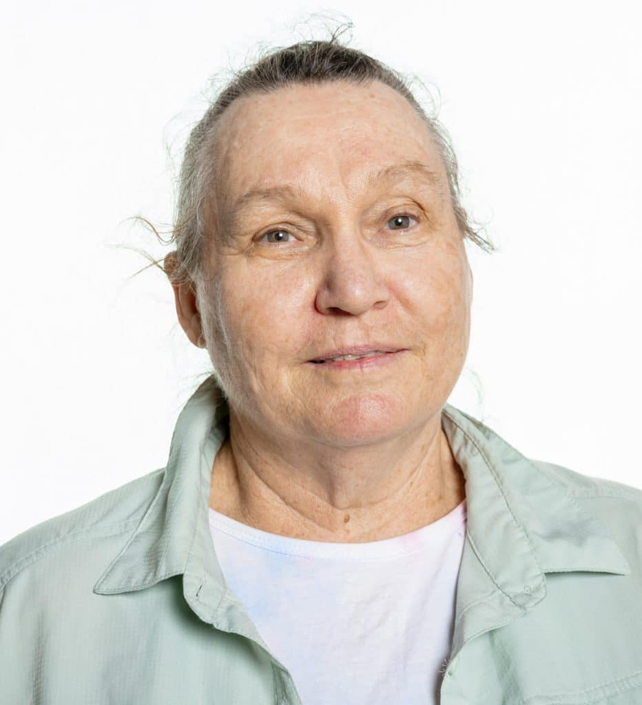 A white woman with her hair pulled back, wearing a white shirt with a mint green collared shirt over it. She is slightly smiling while looking at the camera.