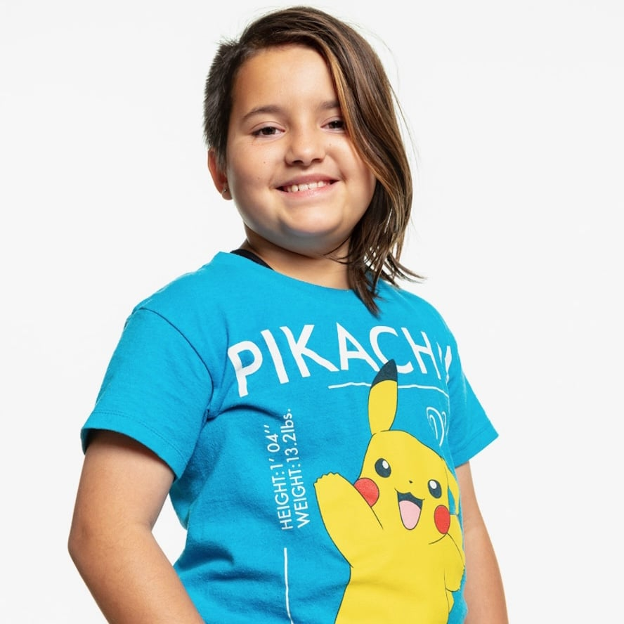 A young Cuban kid wearing a blue Pikachu shirt with half of their head shaved is smiling at the camera.