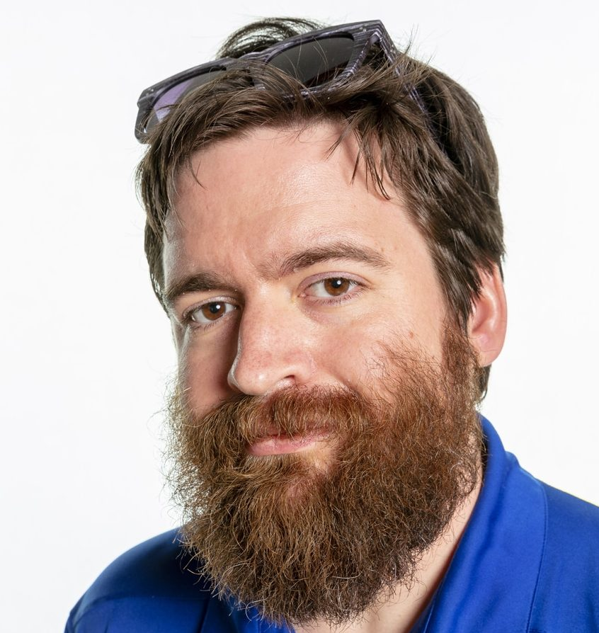 A white man with relish brown hair and a full beard is wearing a blue collared shirt and sunglasses atop his head.