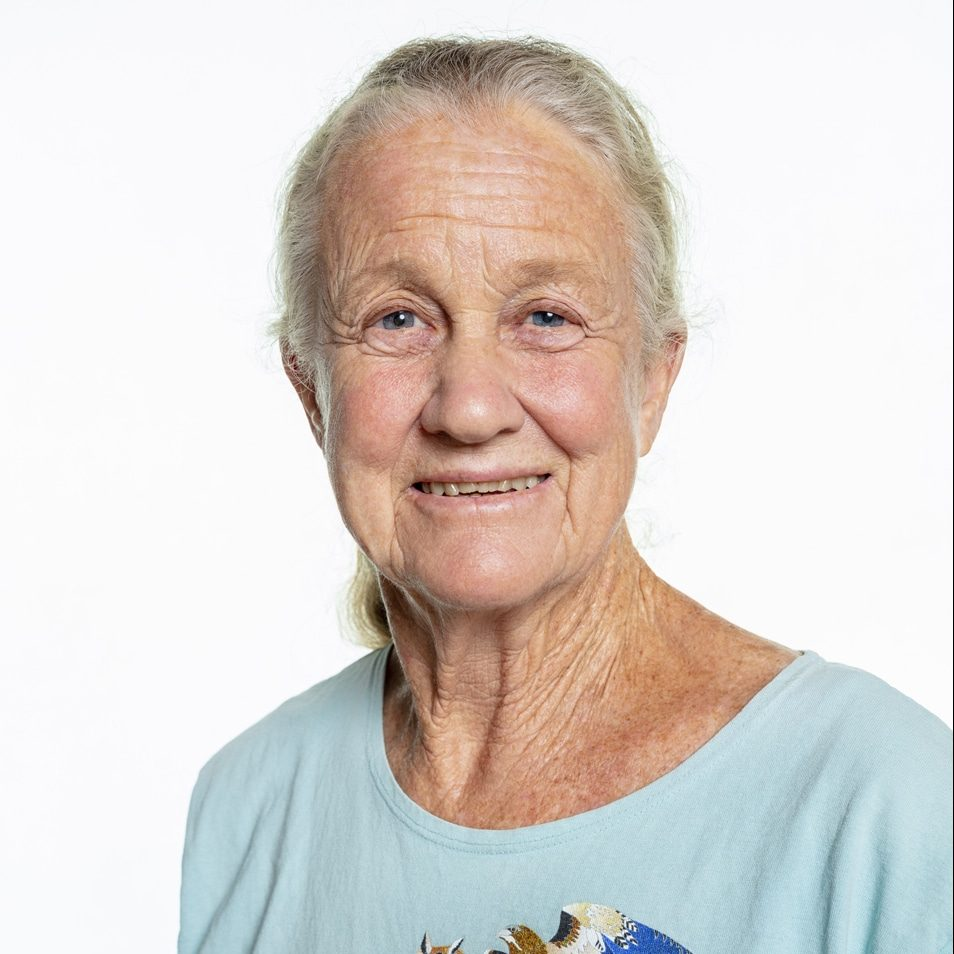 A woman with fair skin and long, white hair pulled back, is wearing a light blue t-shirt and smiling at the camera.