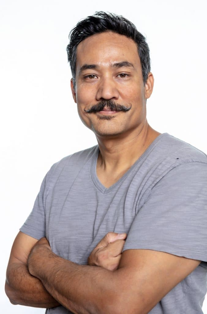 A Mexican American man with black hair, a handlebar mustache and gray shirt is smirking at the camera with his arms crossed.