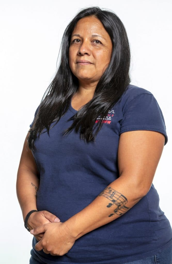 A woman with brown skin and black hair is wearing a blue shirt and looking at the camera. She has a musical note tattoo on her left arm.
