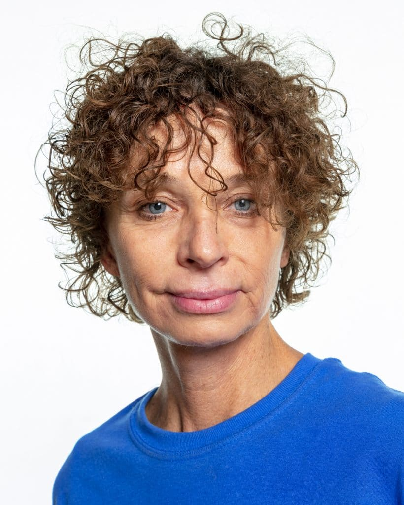 A woman with short curly brown hair, light skin, and blue eyes is wearing a blue t-shirt and looking at the camera with a slight smile.